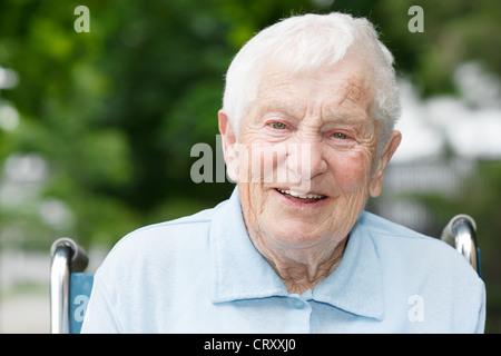 Glücklich älteren Dame im Rollstuhl lächelnd außerhalb - Stockfoto