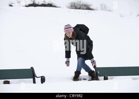 Junge Frau, die Vermeidung von Tiefschnee, Parkbank im verschneiten Tromsø, Norwegen zu erreichen - Stockfoto