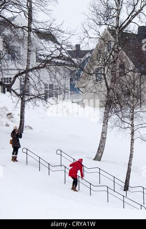 Junge Frau fotografiert wie ihre Freundin hängt auf Handlauf zu rutschen auf die Schritte im verschneiten Tromsø, - Stockfoto