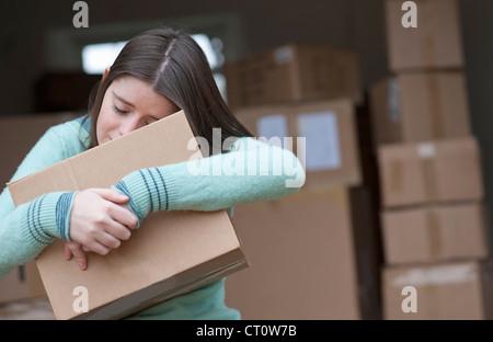 Teenager-Mädchen umarmt Karton - Stockfoto