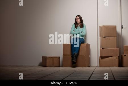 Teenager-Mädchen sitzen auf Karton - Stockfoto