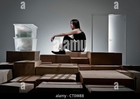 Teenager-Mädchen sitzen auf Kartons - Stockfoto