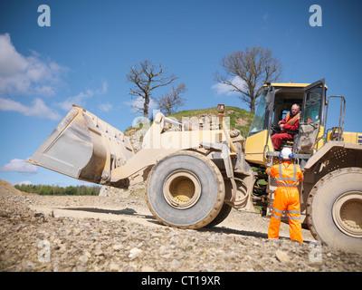 Arbeiter am Bagger im Steinbruch sprechen - Stockfoto