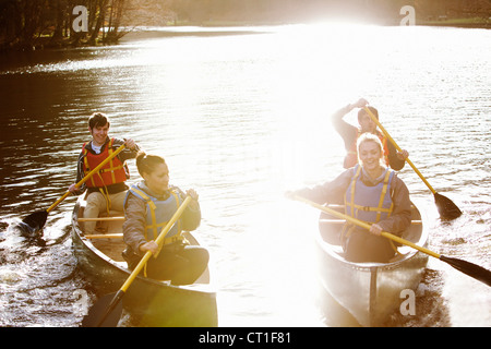 Freunde, die Kanus auf noch See rudern - Stockfoto