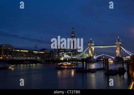 Abends Blick auf Tower Bridge Aufhebung Barrieren Flussschifffahrt und Boote passieren lassen. Blick auf die Scherbe - Stockfoto