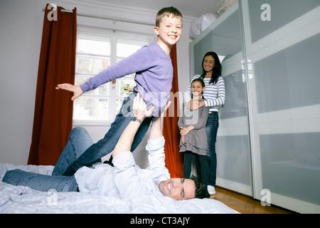 Vater und Sohn spielen auf Bett - Stockfoto