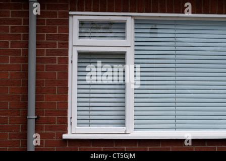 Weiße Fenster mit geschlossenen weiße Jalousie in roten Backsteinmauer mit grauen Kunststoff Regenrinne - Stockfoto