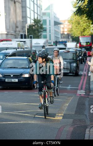 Radfahrer fahren durch beschäftigt Verkehr in der Stadt von London, England. - Stockfoto