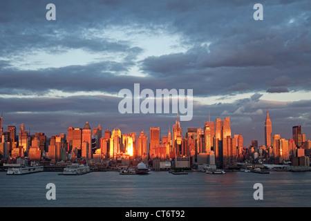 Farbfoto von Midtown Manhattan, New York City Skyline bei Sonnenuntergang mit dem Hudson River von New Jersey aus - Stockfoto