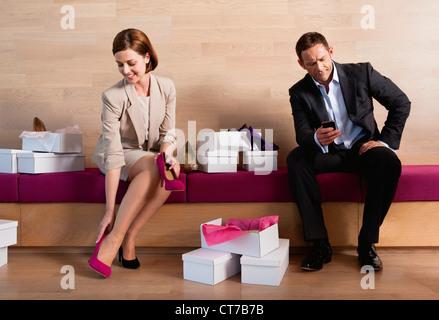 Frau versucht auf Schuhe im Schuhgeschäft, langweilig Mann SMS - Stockfoto