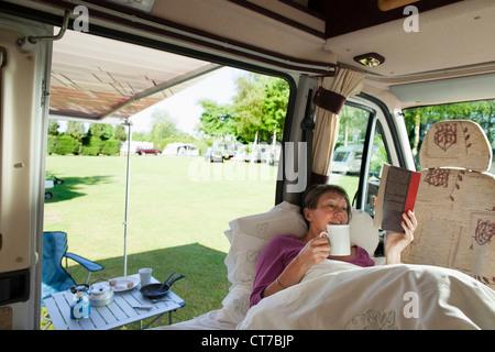 Reife Frau liest in Wohnmobil - Stockfoto