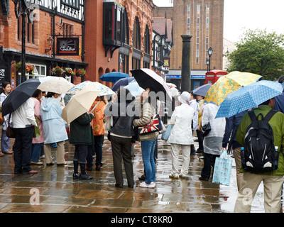 Touristen mit regenschirm im strömenden regen mit meer teleskop