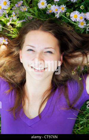Teengirl im Rasen mit Blumen liegen - Stockfoto