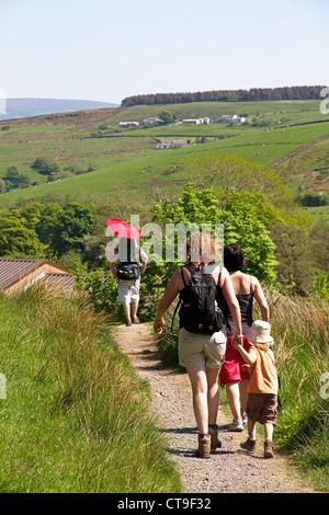 Wandern mit Kindern (einer im Rucksack) planmäßig von Pendle Hill Gerste Dorf, Lancashire, England, UK - Stockfoto