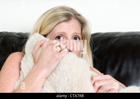Nahaufnahme eines attraktiven jungen kaukasischen Frau versteckt sich hinter Kissen auf Sofa, Konzept, verängstigt - Stockfoto