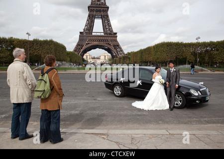 Ausländische Touristen Blick auf ein chinesisches Paar posieren, Hochzeitsfotos in dem Marsfeld nahe dem Eiffelturm - Stockfoto