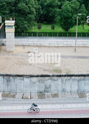 Abschnitt der original Berliner Mauer an der Bernauer Straße mit ehemaligen Todesstreifen und Wachturm in Berlin - Stockfoto