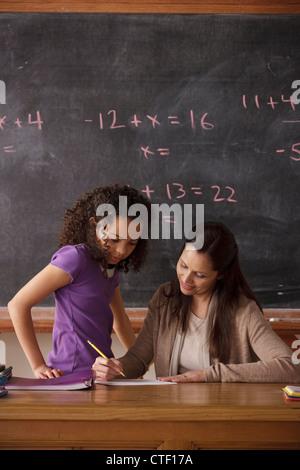 USA, California, Los Angeles, Schulmädchen (10-11) und Lehrer mit Tafel im Hintergrund - Stockfoto
