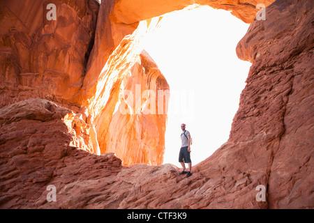 USA, Utah, Moab, Mitte erwachsener Mann posiert vor natürlichen Bögen - Stockfoto