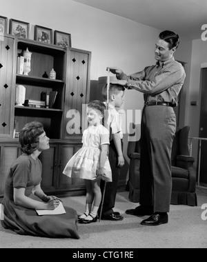 1960ER JAHREN VATER MESS TOCHTER & SOHN RÜCKEN AN RÜCKEN MIT MUTTER AUFZEICHNUNG VON INFORMATIONEN - Stockfoto