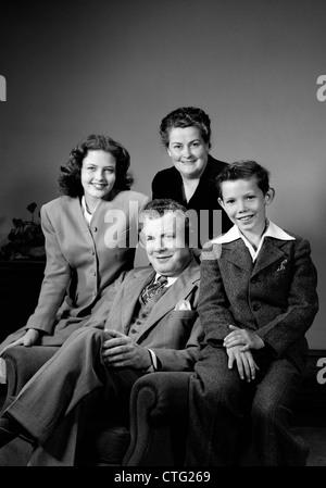 1940ER JAHRE PORTRAIT FAMILIE MUTTER VATER TOCHTER SOHN SITZEN ZUSAMMEN AUF STUHL STUDIO - Stockfoto