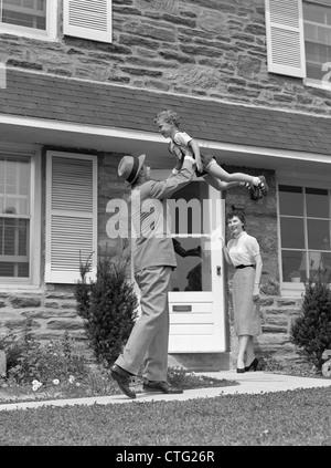 1950S 1960S VATER HEIMKEHREN HEBEN SOHN IN LUFT WÄHREND FRAU AUS TÜR SCHAUT - Stockfoto