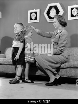 1950ER JAHREN MUTTER MESSUNG UNTERSCHIED IN DER HÖHE ZWISCHEN SOHN UND TOCHTER INDOOR - Stockfoto