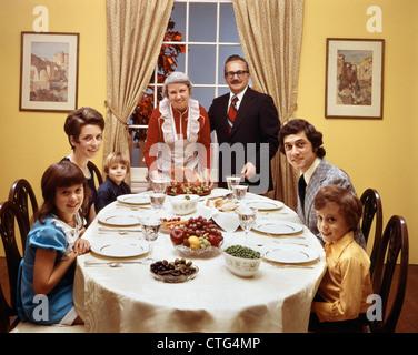 1970ER JAHRE-3 GENERATIONEN-FAMILIE SITZT AM ESSTISCH MIT BLICK IN DIE KAMERA - Stockfoto