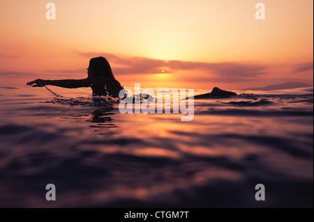 Eine Frau Paddeln auf einem Surfbrett bei Sonnenuntergang; Tarifa, Cádiz, Andalusien, Spanien - Stockfoto