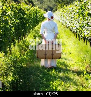 eine Frau in einem weißen, spaziert durch Weinberge viktorianischen Kleid - Stockfoto