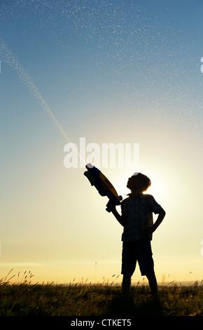 Junge schießen eine Wasserpistole bei Sonnenuntergang. Silhouette. UK - Stockfoto