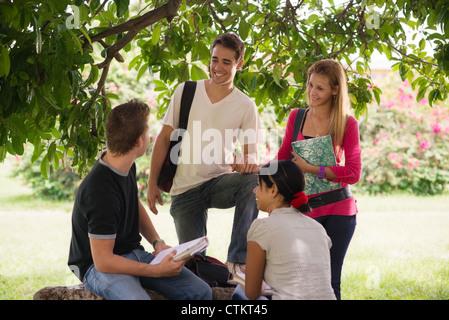 Menschen und Bildung, College-Studenten treffen und Hausaufgaben zusammen im park - Stockfoto
