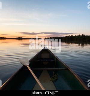 Ein Boot und Paddel auf einem ruhigen See bei Sonnenuntergang; Lake Of The Woods, Ontario, Kanada - Stockfoto