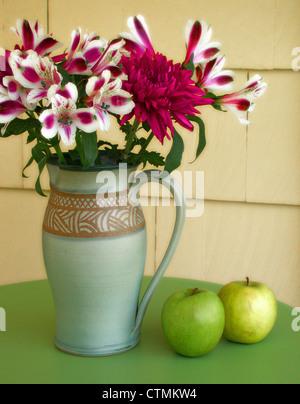 Rote und weiße Blüten (Azaleen) in einer Vase auf einem Tisch neben grünen Äpfeln, Vermont USA