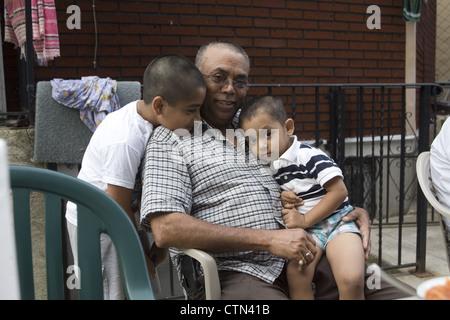 Junge Jungs zeigen ihre Zuneigung zu Opa in einem Hinterhof in Brooklyn, New York zu sammeln. - Stockfoto