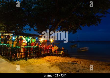 Touristen genießen bunt beleuchteten Strand Bar in der Nacht in der Karibik auf Little Corn Island, Nicaragua. - Stockfoto