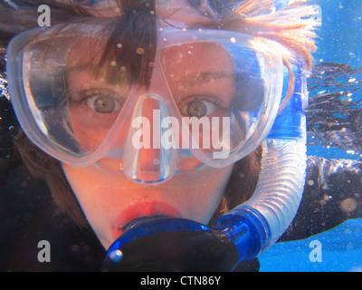 Nahaufnahme des zehn Jahre alten Jungen schauen erstaunt Schnorchel-Ausrüstung unter Wasser tragen. - Stockfoto