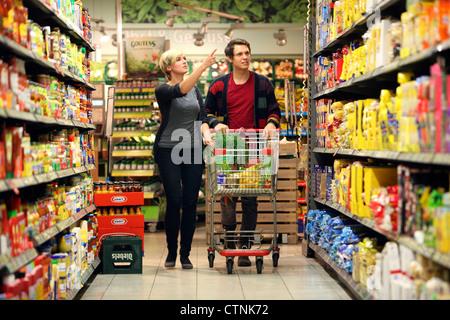 Ein junges Paar in einem großen Supermarkt, mit einem Wagen, zu Fuß durch die Gänge mit Regale voller Lebensmittel - Stockfoto