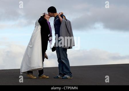 Ein Bräutigam trägt seinen Anzug und eine Braut trägt ihr weißes Kleid sind am Tag ihrer Hochzeit küssen. - Stockfoto