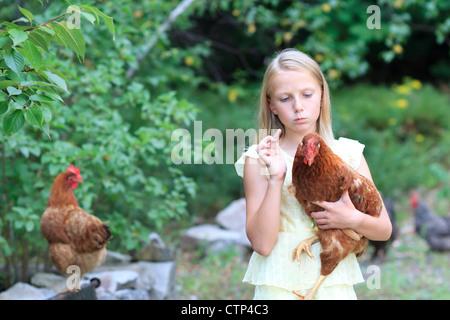Junge blonde Mädchen im Garten mit Hühnern in einem gelben Kleid - Stockfoto