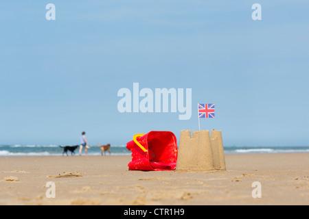 Union Jack-Flagge in eine Sandburg neben einem Childs Eimer und Schaufel an einem Strand. England - Stockfoto