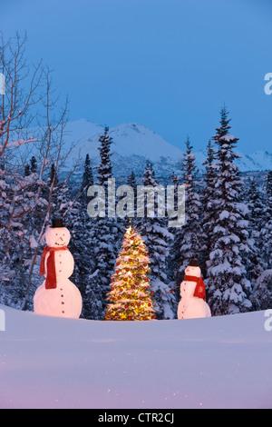 Foto erwachsenes Kind Schneemänner mit roten Schal schwarz Top hüten stehend nahe beleuchtet Weihnachten Baum rot - Stockfoto
