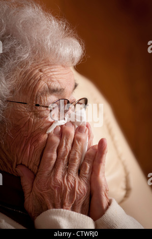 Ältere Frau hält eine Gewebe und Weinen