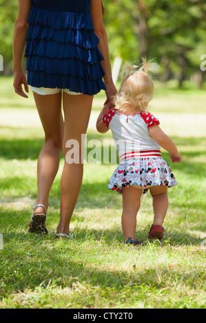 Mutter an Hand der ihre weiblichen Kleinkind bei einem Spaziergang in einem park - Stockfoto