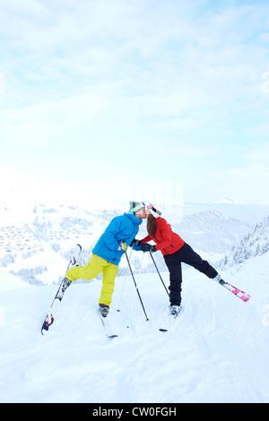 Skifahrer auf verschneite Berggipfel küssen - Stockfoto