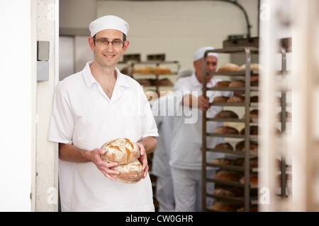 Koch hält Brote in Küche - Stockfoto