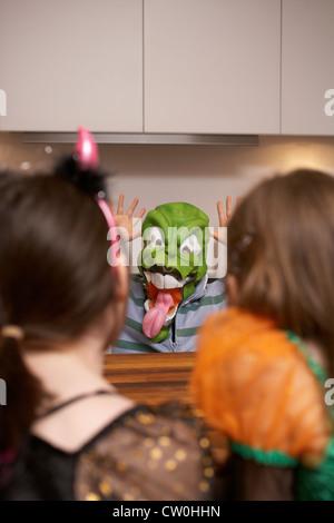 Junge mit Halloweenmaske in Küche - Stockfoto