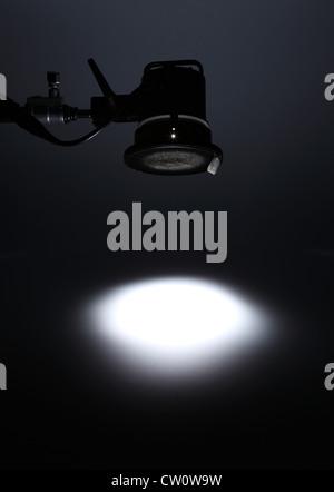 Eine fotografische Licht von oben einen weißen Spot auf einem leeren dunklen Hintergrund zu erstellen. - Stockfoto