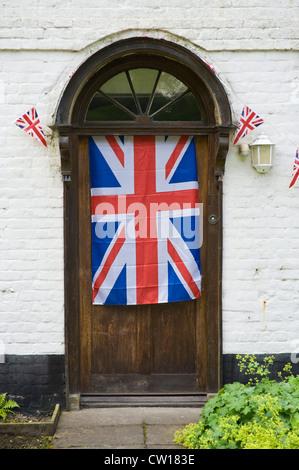 Union Jack-Flagge und Girlanden hängen an Eingangstür des historischen Gebäudes im Dorf von Brampton Bryan Herefordshire - Stockfoto