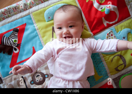 Glückliches Baby auf bunte Spieldecke - Stockfoto